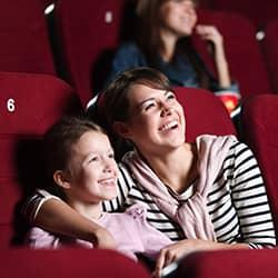 a mother hugging her daughter while sitting in the movie theater during a showing totaly un awar of the bed bug infestation around them