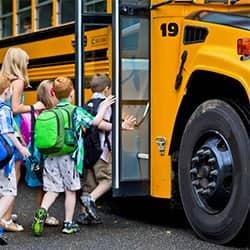 a full class of chidren boarding a large yellow school bus on their first day of school fully un aware of the bed bug hitchhiking their way on their next host