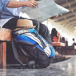 a new castle resident reading a newspaper at a train stop unaware of the hitchhiking bed bugs infesting his backpack