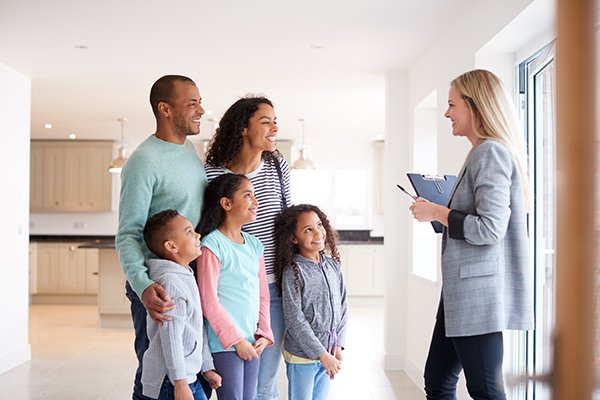 a happy family of five and a real estate agent inside of a home for sale in pennsylvania