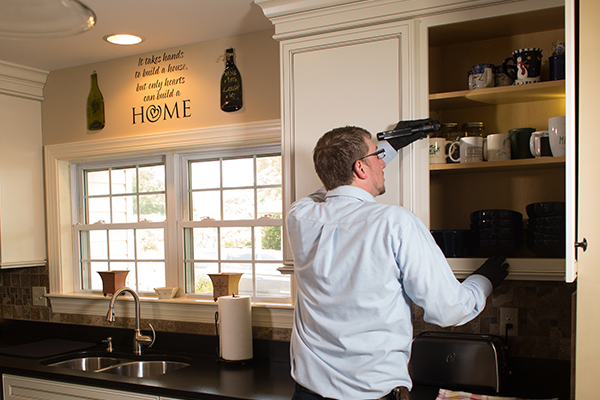 exterminator inspecting kitchen cupboards in a lansdowne home for pest activity