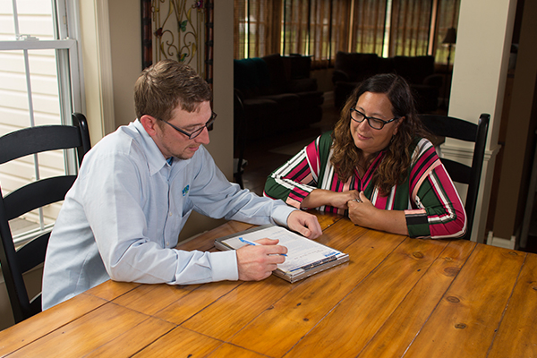 a mosquito control technician meeting with a customer in her home in lower salford pennsylvania