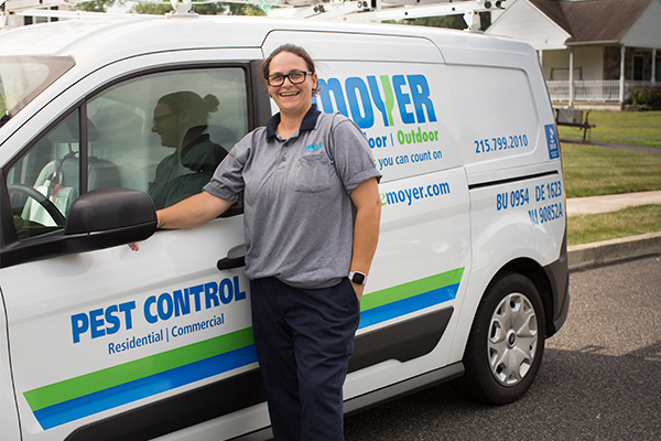 a pest control employee standing by her service vehicle in roslyn pennsylvania