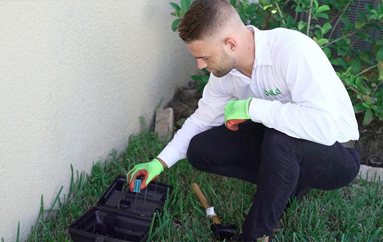 tehcnician kneeling over rodent bait box