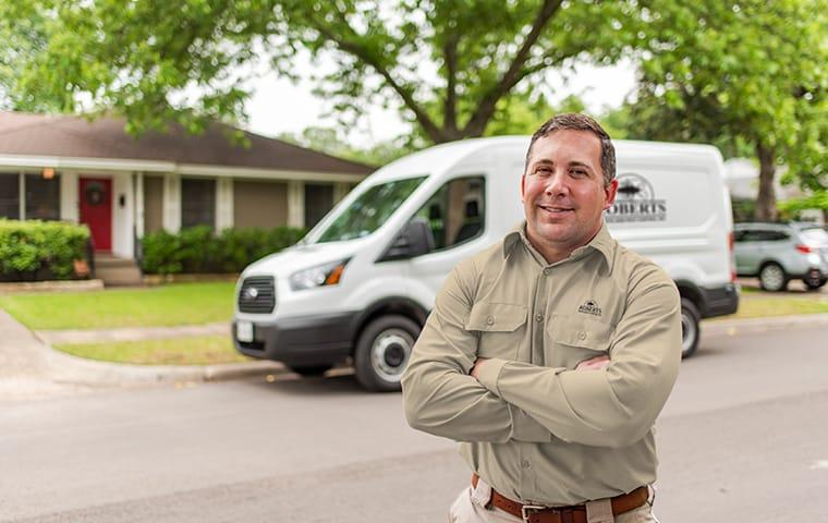 a pest technician standing in front of his service vehicle in austin texas