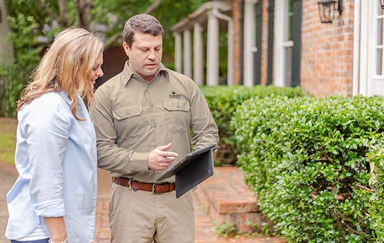 a pest technician talking with a customer outside her home in austin texas
