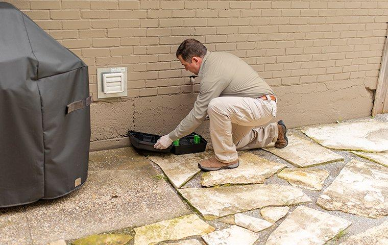 a service technician checking a rodent trap outside of a home in lakeway texas
