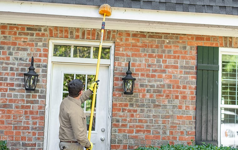 a pest technician removing spider webs from the front of a house in round rock texas