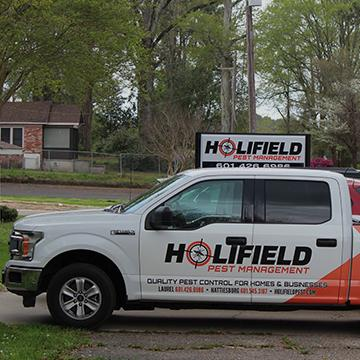 a holifield pest management company vehicle parked outside in laurel mississippi