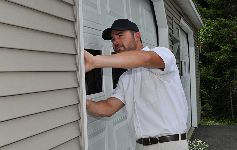 a holifield service technician inspecting the exterior of a home in leakesville long beach