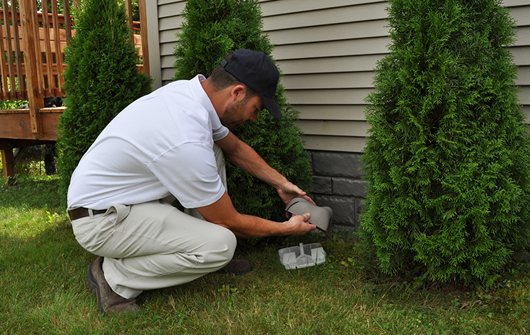 a holifield pest management service technician setting up a rodent station outside a home in long beach mississippi