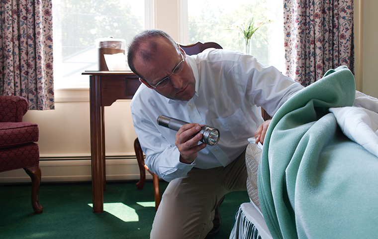 a holifield pest management service technician inspecting for bed bugs in a montrose mississipi home