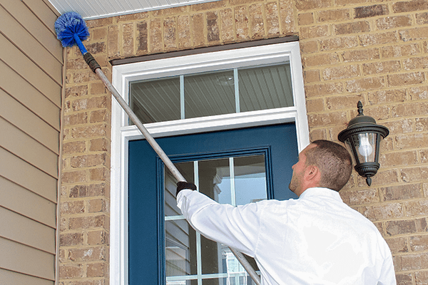 a pest technician sweeping the exterior of a roanoke home