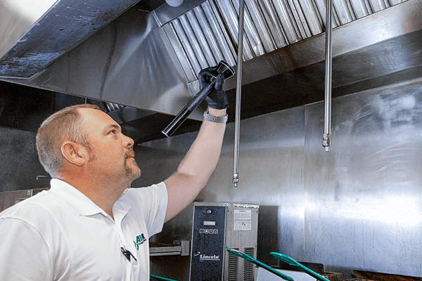 a pest technician inspecting the inside of a commercial kitchen