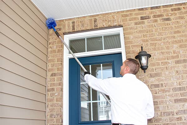 an all pest service technician treating the exterior of a home in christiansburg virginia