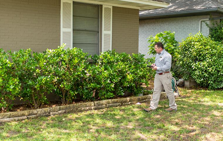 a pest technician performing an exterior inspection at a home in castaic california