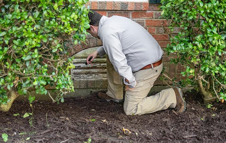 a pest technician inspecting the exterior of a home in valencia california