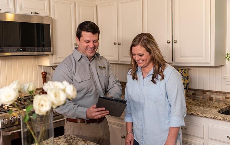 a pest technician meeting with a customer in her kitchen in santa clarita california