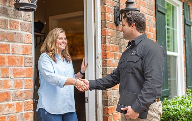 pest control tech greeting roanoke homeowner during follow up service