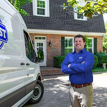 a jury pest services technician standing outside of a home in richmond county georgia