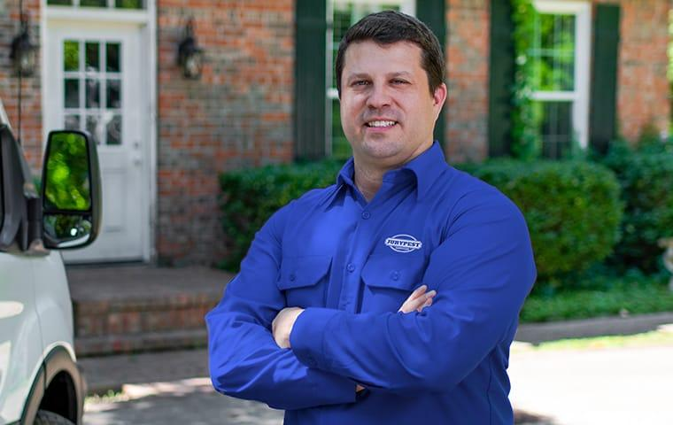 a jury pest services technician standing outside of a home in aiken south carolina