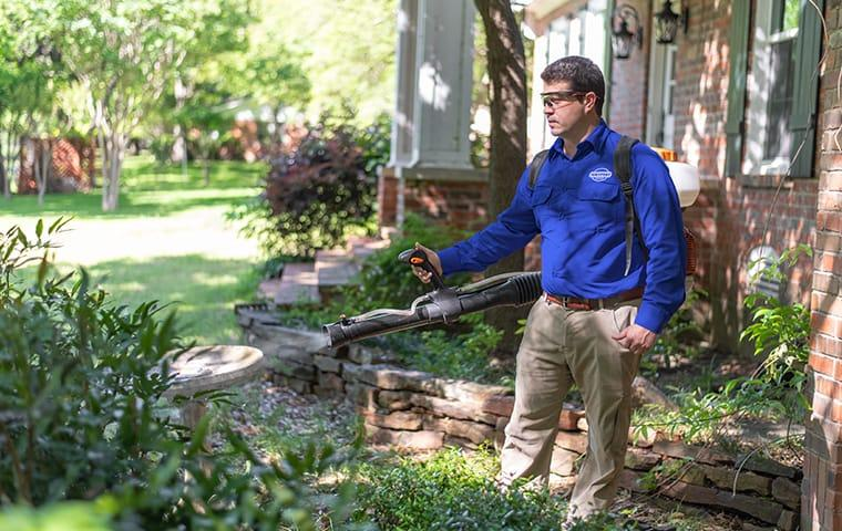 a service technician performing a mosquito treatment outside a home in aiken south carolina
