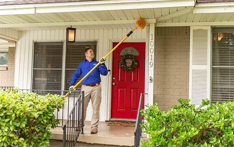 a service technician clearing spider webs away at a home in lexington south carolina