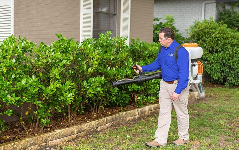 a service technician performing an exterior treatment at a home in aiken south carolina