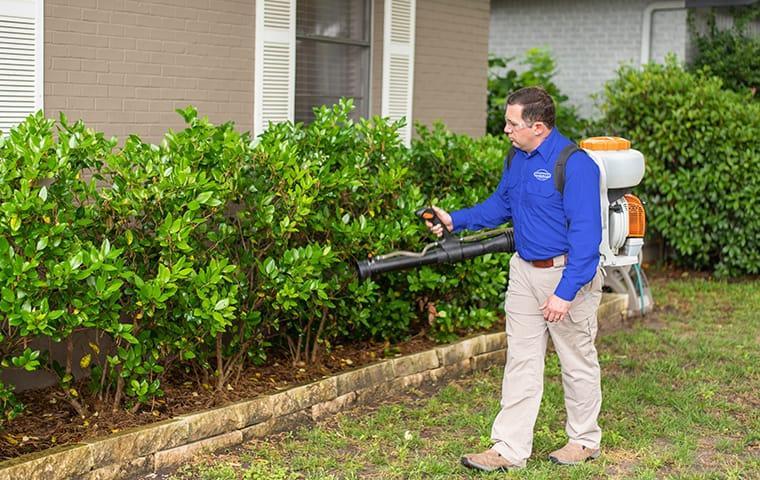 a service technician performing an exterior treatment at a home in aiken south carolina