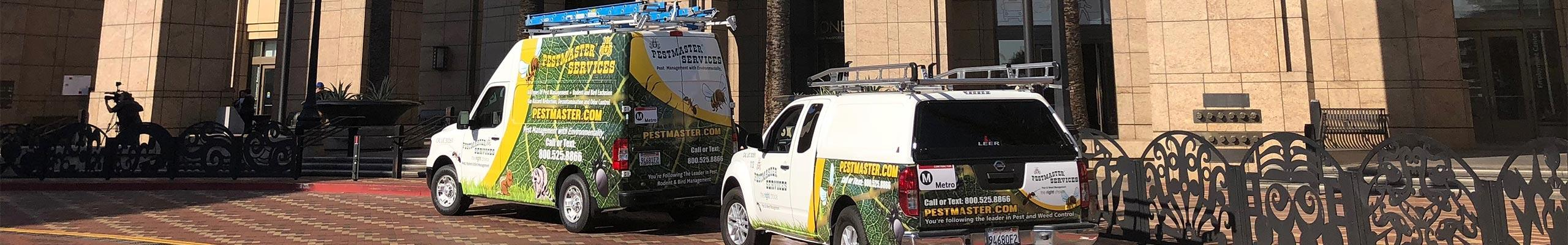 two pestmaster services company vehicles parked outside a commercial building