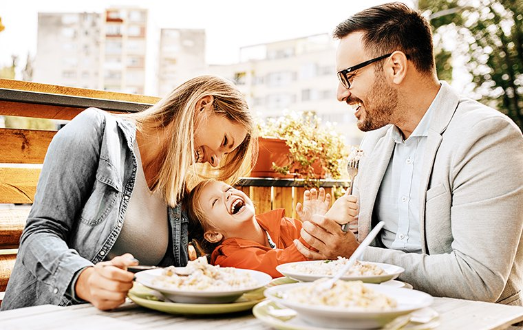 a small family eating and laughing at a restaurant