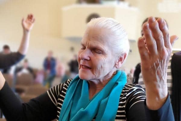 woman lifting hands in worship to god