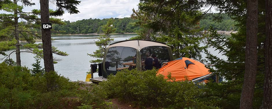 campers enjoying lunch in tent overlooking the water