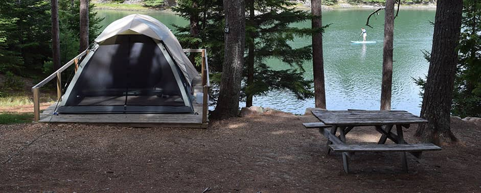 tent and picnic table close to the water