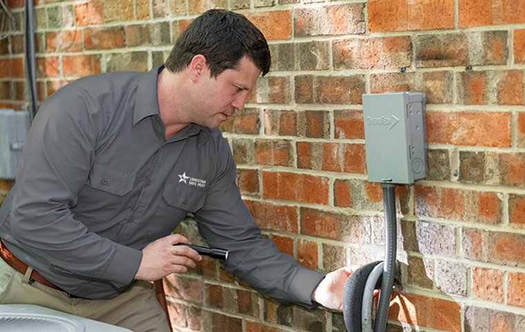 a pest control service technician inspecting the perimeter of a home for pests