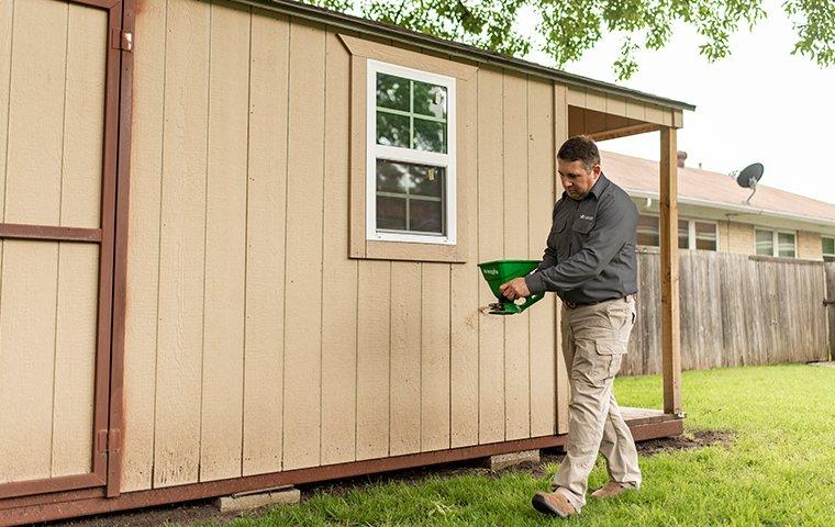 a pest control service technician inspecting the exterior of a home for pests