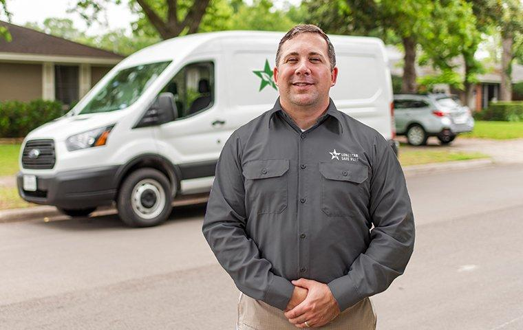 a pest control service technician standing outside of a home