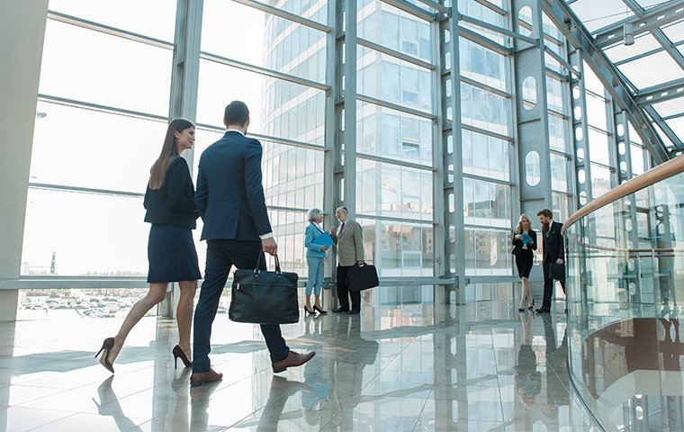 a man and a woman walking inside a large office building