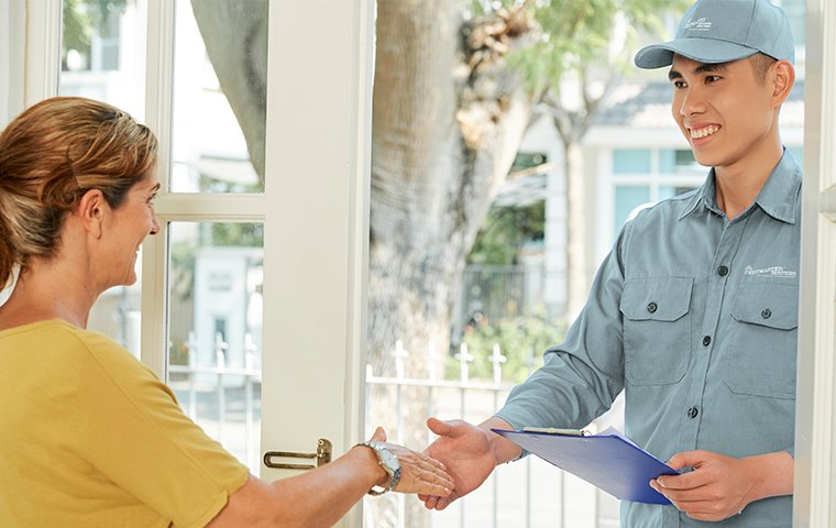 a friendly pest tech discussing services with a homeowner