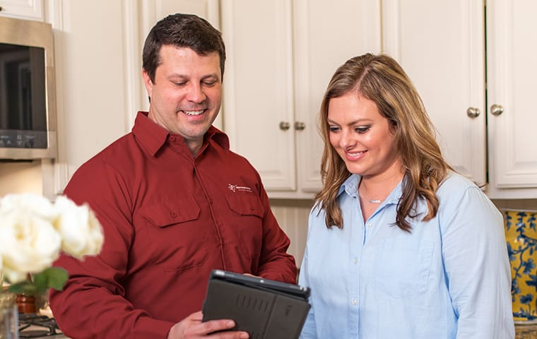 a technician and a homeowner using a tablet in frisco texas