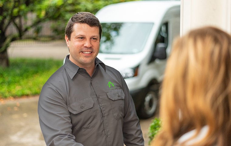a termite control expert talking with a customer outside her home in hendersonville north carolina