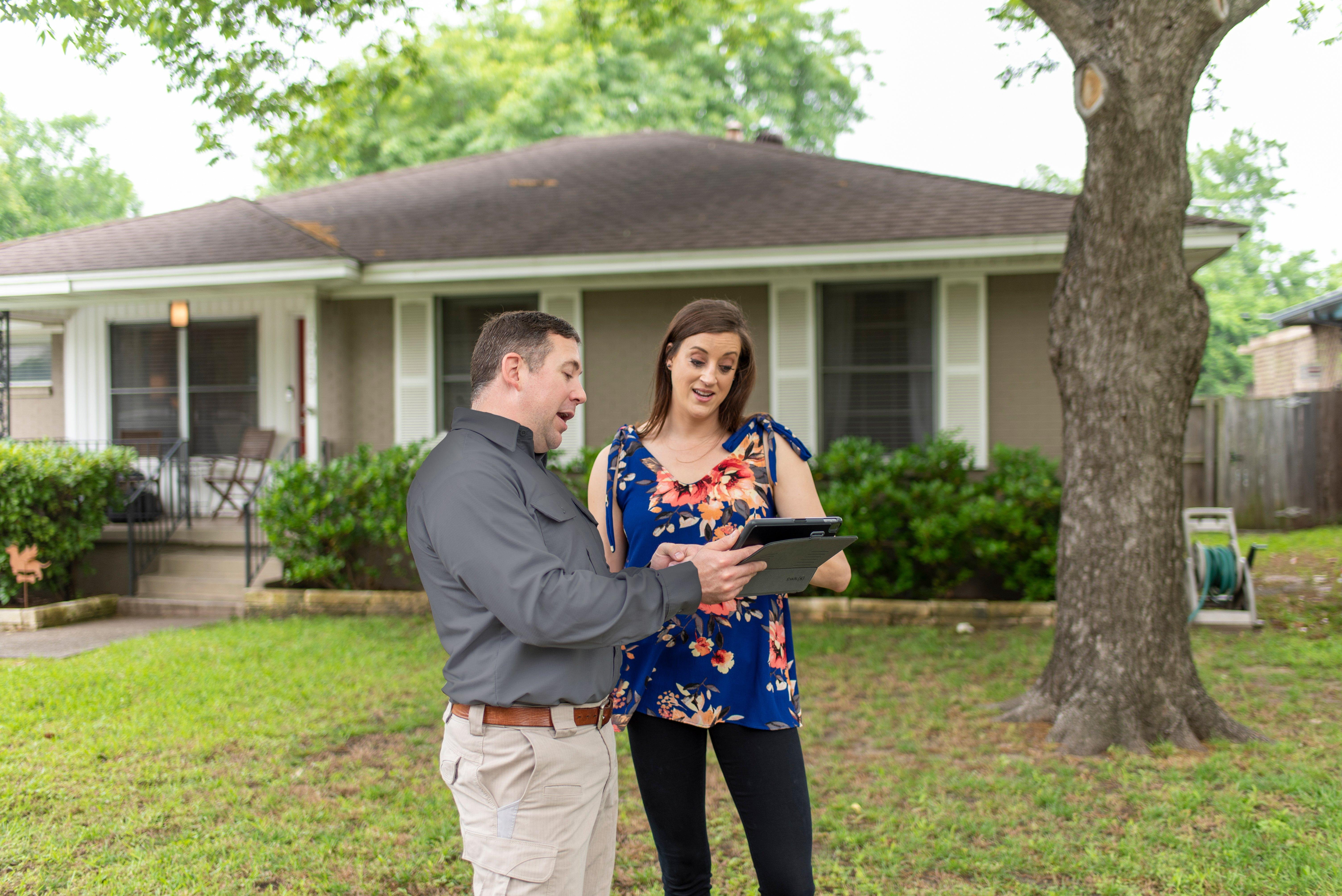 a pest control expert talking with a customer outside her home in hendersonville north carolina