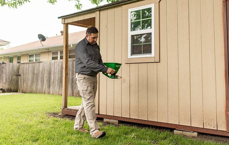 a pest expert treating for termites outside of a home in hendersonville north carolina