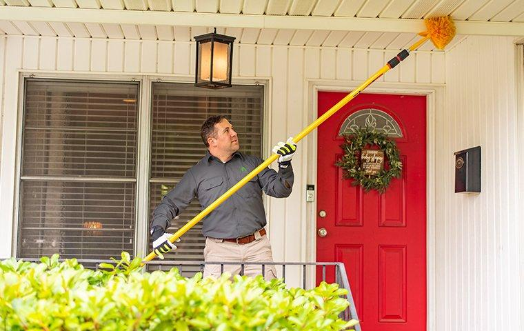 a pest control technician removing spider webs from the doorway of a home in hendersonville north carolina