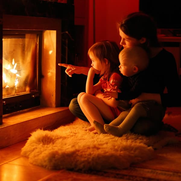 family enjoying a warn evening by the fireplace