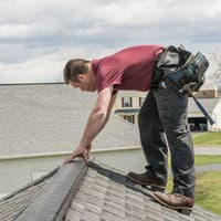 pest control technician fixing roof