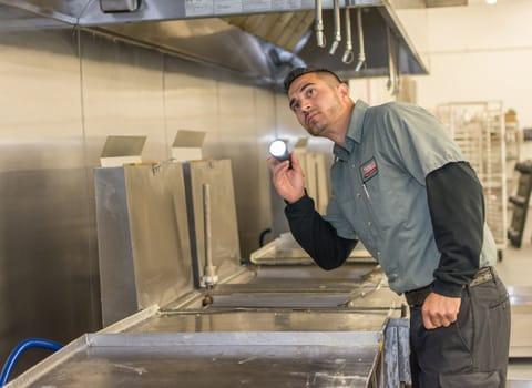 pest control tech inspecting a restaurant kitchen