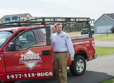 thomas pest control service technician standing near a company truck parked outside of a home in stillwater new york