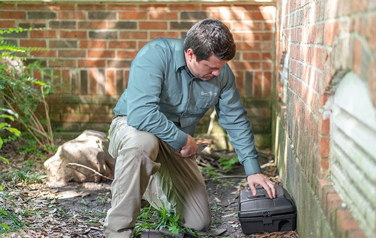 a pest technician inspecting a rodent station