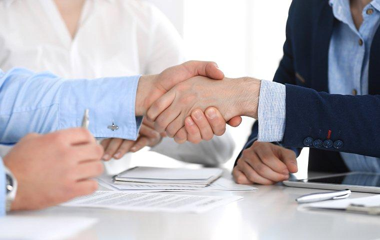 business people shaking hands over a franchise deal with pestmaster